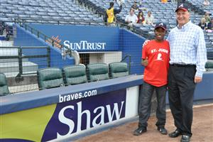 Randy Merritt, President of Shaw Industries, and St. Jude patient Archie at Atlanta Braves Game.